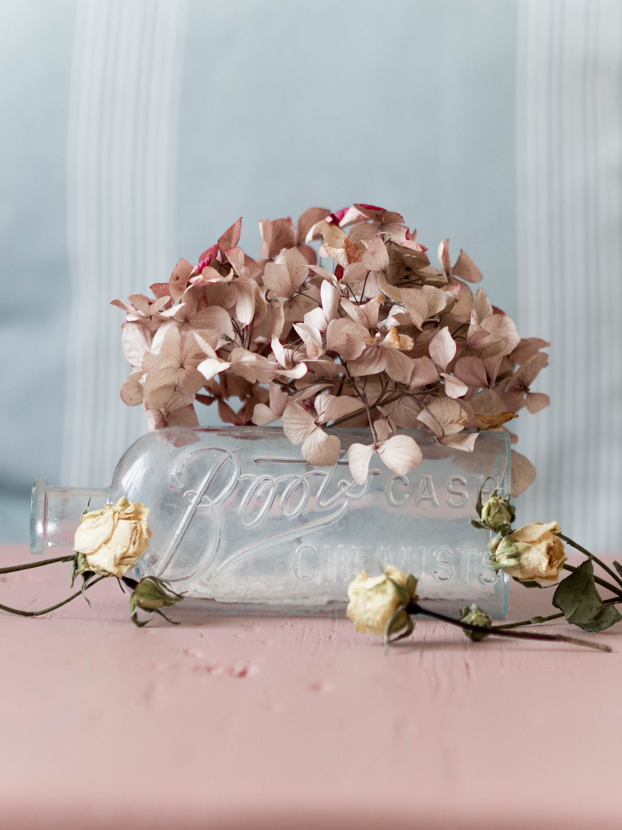 Vintage glass bottle from Boots Cash Chemist on pink table with dried cream roses and dried pink hydrangea